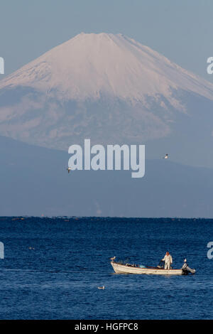 A fisherman in a small boat in front of a snow capped Mount Fuji from Muira, Kanagawa, Japan. Saturday December - Stock Photo