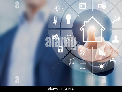 Circular futuristic interface of smart home automation assistant on a virtual screen and a user touching a button - Stock Photo