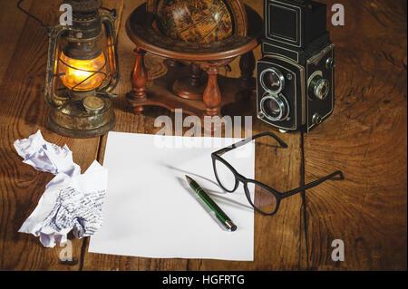 Vintage still life stuff on a rustic wooden table,retro camera, glasses, pencil, pen, old rusty kerosene lamp. - Stock Photo