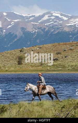Gaucho on horse by lake at Estancia Alta Vista, El Calafate, Parque Nacional Los Glaciares, Patagonia, Argentina, - Stock Photo