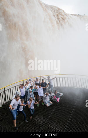 Children posing for group photo below Iguazu Falls from Brazilian side, Iguazu National Park, Brazil, South America - Stock Photo