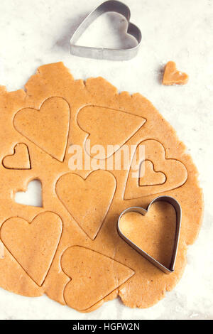 Making homemade heart shaped cookies from ginger raw dough - festive homemade cookies pastry for Valentine day - Stock Photo