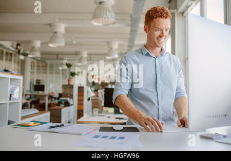 Shot of happy young man standing at his desk and working on computer. Businessman working in modern office. - Stock Photo