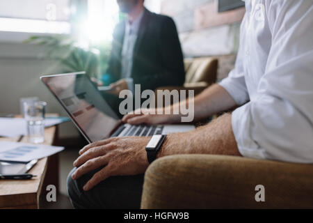 Businessman working on laptop during corporate meeting. Business people having a meeting in office. - Stock Photo