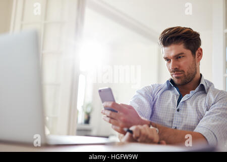 Shot of relaxed young man sitting at desk using mobile phone. Handsome caucasian man reading text message on his - Stock Photo