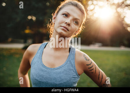 Close up portrait of fit woman standing outdoors and looking away. Confident fitness model in park. - Stock Photo