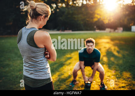 Female trainer standing in the park with young man doing weight training with kettlebell in background. - Stock Photo