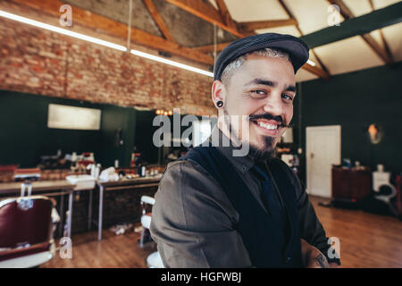 Close up of successful young man with cap in salon. Handsome hairdresser smiling at barbershop.