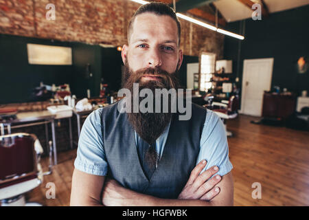 Young barber at his barbershop. Man standing with his arms crossed and staring at camera. - Stock Photo