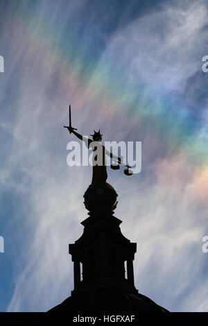 Lady Justice atop the Old Bailey in London, silhouetted against a vibrant blue sky with a faint rainbow. - Stock Photo