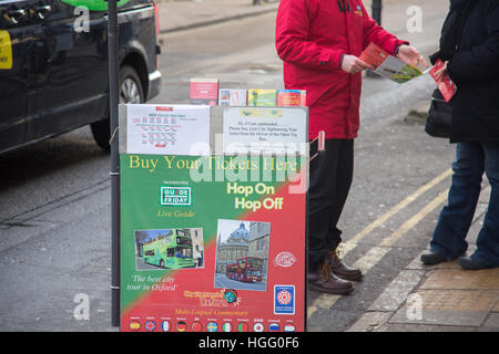 Man selling tour bus tickets for sightseeing ride around Oxford,England - Stock Photo