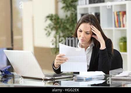 Worried businesswoman reading a notification sitting in a desktop at office - Stock Photo