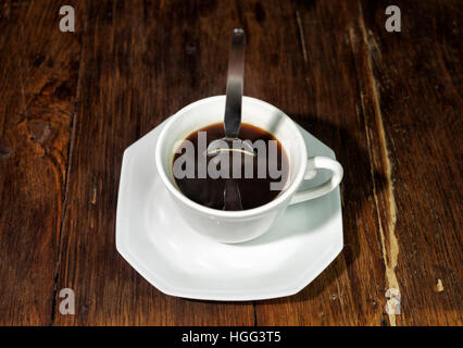 Spoon standing upright in a cup of strong coffee - Stock Photo