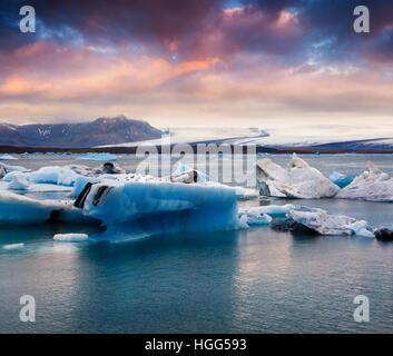 Floating of blue icebergs in Jokulsarlon glacial lagoon. Colorful sunset in Vatnajokull National Park, southeast - Stock Photo