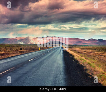 Empty asphalt road with colorful cloudy sky. Beautiful outdoor scenery in the Hverarond geothermal valley, Iceland, - Stock Photo