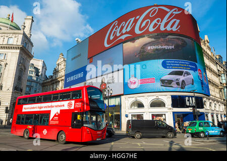 LONDON - NOVEMBER 11, 2016: Classic red double-decker bus passes in front of billboards advertising Coca--Cola and - Stock Photo