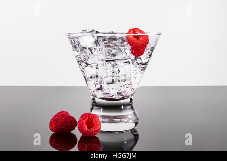 Sparkling beverage in a martini glass with raspberries - Stock Photo