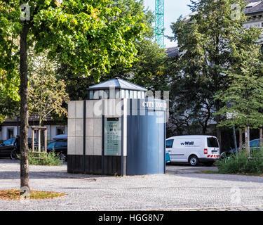 Germany, Berlin, Neukölln. Public toilets in leafy square in Bohemian Village Rixdorf - Stock Photo