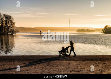 Kladow, Berlin. Young woman pushing pram in golden light next to Havel river which feeds the Wannsee Lake - Stock Photo