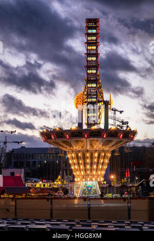 Berlin, Mitte. illuminated funfair rides, ferris wheel and carousel at traditional German Christmas market - Stock Photo