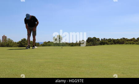 A golfer lines up a shot on the putting green - Stock Photo