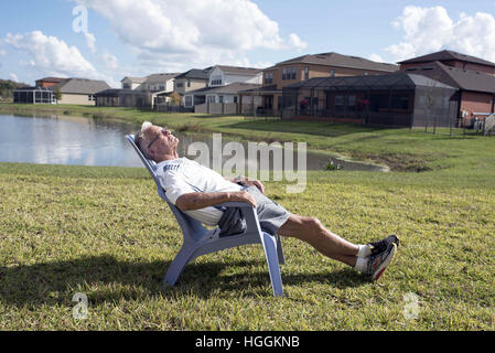 Wesley Chapel, FL, USA. 24th Dec, 2016. Retired executive his 80s relaxes in sunshine outside new home in a suburban - Stock Photo