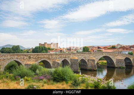 Medieval bridge over river Tormes and view of the castle and village. El Barco de Avila, Avila province, Castilla - Stock Photo