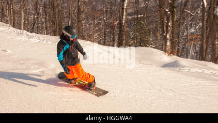 Young rider going down the mountain - Stock Photo