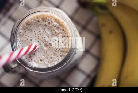 Healthy smoothie. Banana,oats,Chia seeds and honey mix. Bananas in background, Top view. - Stock Photo
