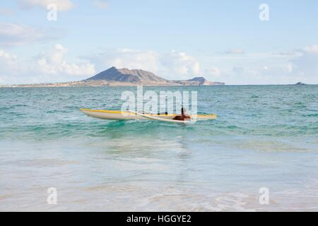 A man inspects his outrigger canoe in the surf before paddling out on his next tropical adventure. - Stock Photo
