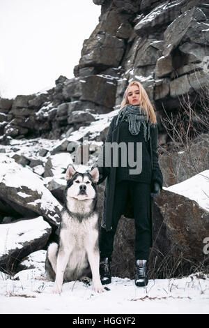 Girl with dog Malamute among rocks in winter. She is standing among rocks and snow. Dog sits next to her. - Stock Photo