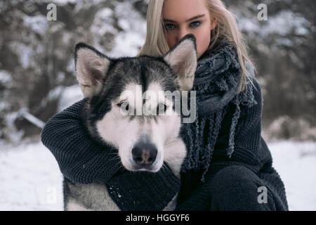 Portrait of girl with  big Malamute dog on winter background. Girl sits next to dog and hugging dog's neck. - Stock Photo