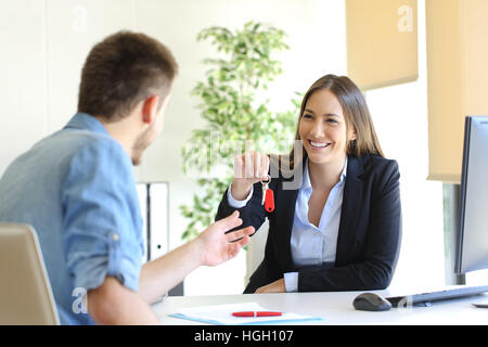 Happy real estate agent giving house keys to a customer after signing contract in the office - Stock Photo