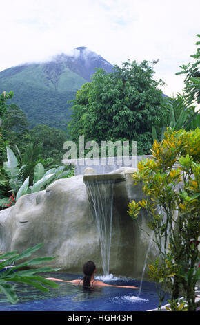 A woman is relaxing in a Thermal bath close to the volcano Arenal, La Fortuna, Costa Rica, Central America - Stock Photo
