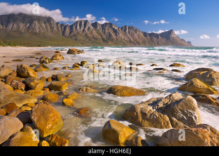A rocky beach at the Kogel Bay in South Africa with the Kogelberg Mountains in the back. Photographed on a very - Stock Photo