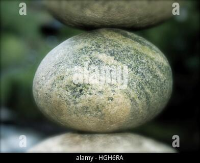 Stuck between a rock and a hard place. River stone suspended between two other stones. - Stock Photo