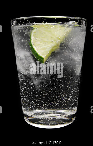 Cold drink with a lime. Could be a gin &Êtonic or vodka tonic. Or just sparkling ice cold water. - Stock Photo