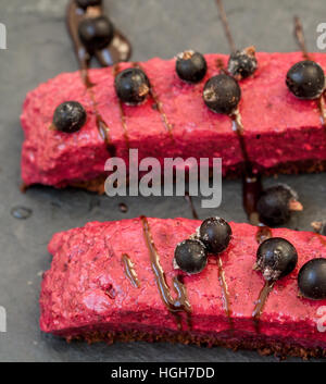 Raw chocolate berry cake with berries and chocolate syrup and currant.  Love for a healthy raw food concept. - Stock Photo