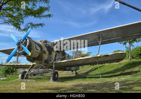 The retired Antonov An-2 military aircraft camouflaged - Stock Photo