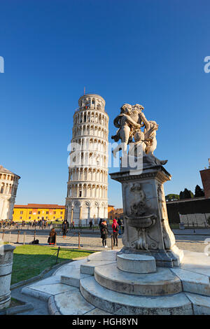 The Leaning Tower of Pisa and The Fountain with Angels on Piazza dei Miracoli in Tuscany - Stock Photo
