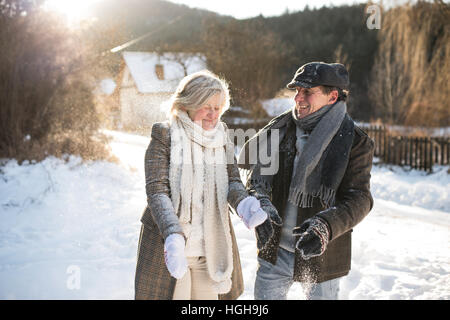 Beautiful senior couple blowing snow in sunny winter nature - Stock Photo
