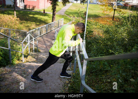 Runner on stairs on sunny autumn day, stretching legs. - Stock Photo