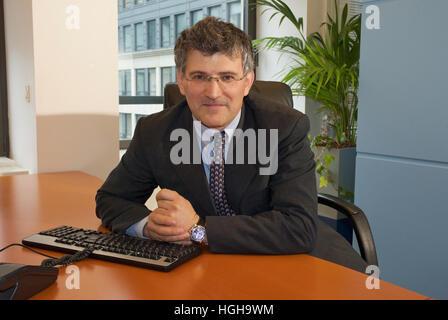 Businessman sitting at a desk seeming keen - Stock Photo