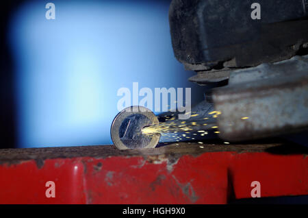 One Euro coin in a vice being cut with an angle grinder - Stock Photo
