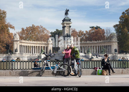 Madrid, Spain: Young couple on a bike ride take a selfie in front of the Monument to Alfonso XII at Buen Retiro - Stock Photo