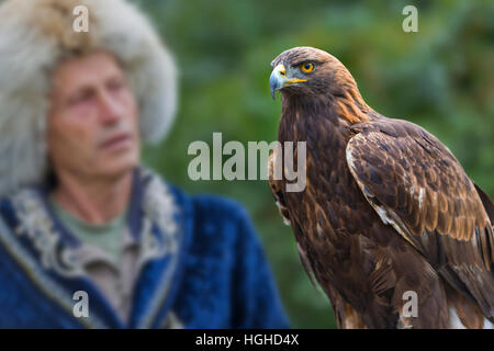 Kazakh eagle hunter in traditional costumes and his golden eagle in Almaty, Kazakhstan. - Stock Photo
