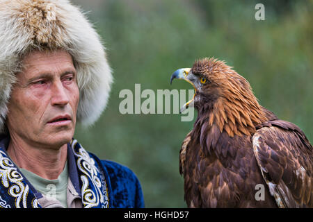 Kazakh eagle hunter in traditional costumes holds his goldeneagle and they look at each other in Almaty, Kazakhstan. - Stock Photo