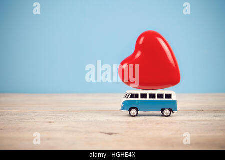 Old vintage toy van with big red heart figure on top in blue background. - Stock Photo