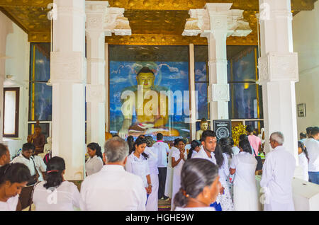 The large statue of Seated Buddha in the Image House of Bodhi Tree Temple, full of pilgrims - Stock Photo