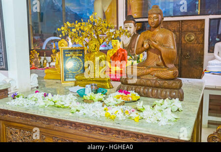 The altar in Image House of Bodhi Tree Temple with small sculptures of Buddha and lotus flowers - Stock Photo